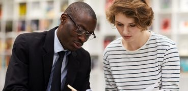 Content confident African-American college consultant in formal suit drawing in clipboard while explaining information to student girl in library